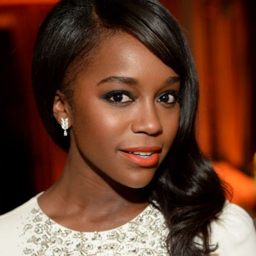 Em um evento da Revista Elle, Aja Naomi King, que interpreta Michaela na série How to Get Away With Murder, apostou no vibrante batom laranja para garantir um toque de cor no look