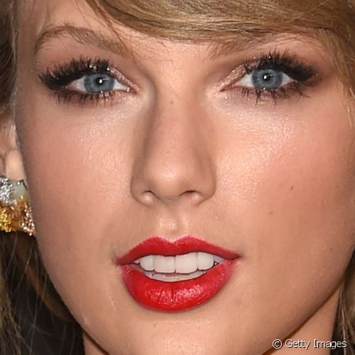 Taylor Swift destacou os lábios com intenso batom vermelho e os olhos com esfumado de sombra bronze para o InStyle And Warner Bros. 72nd Annual Golden Globe Awards Post-Party